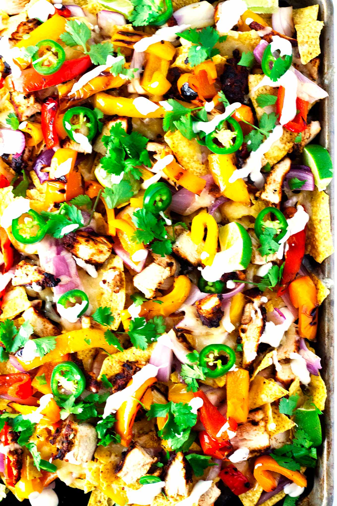 These grilled chicken fajita nachos are beyond delish! Chicken, peppers, and onions all grilled to perfection then topped on top of tortilla chips with cheese and optional toppings have these nachos out of this world!